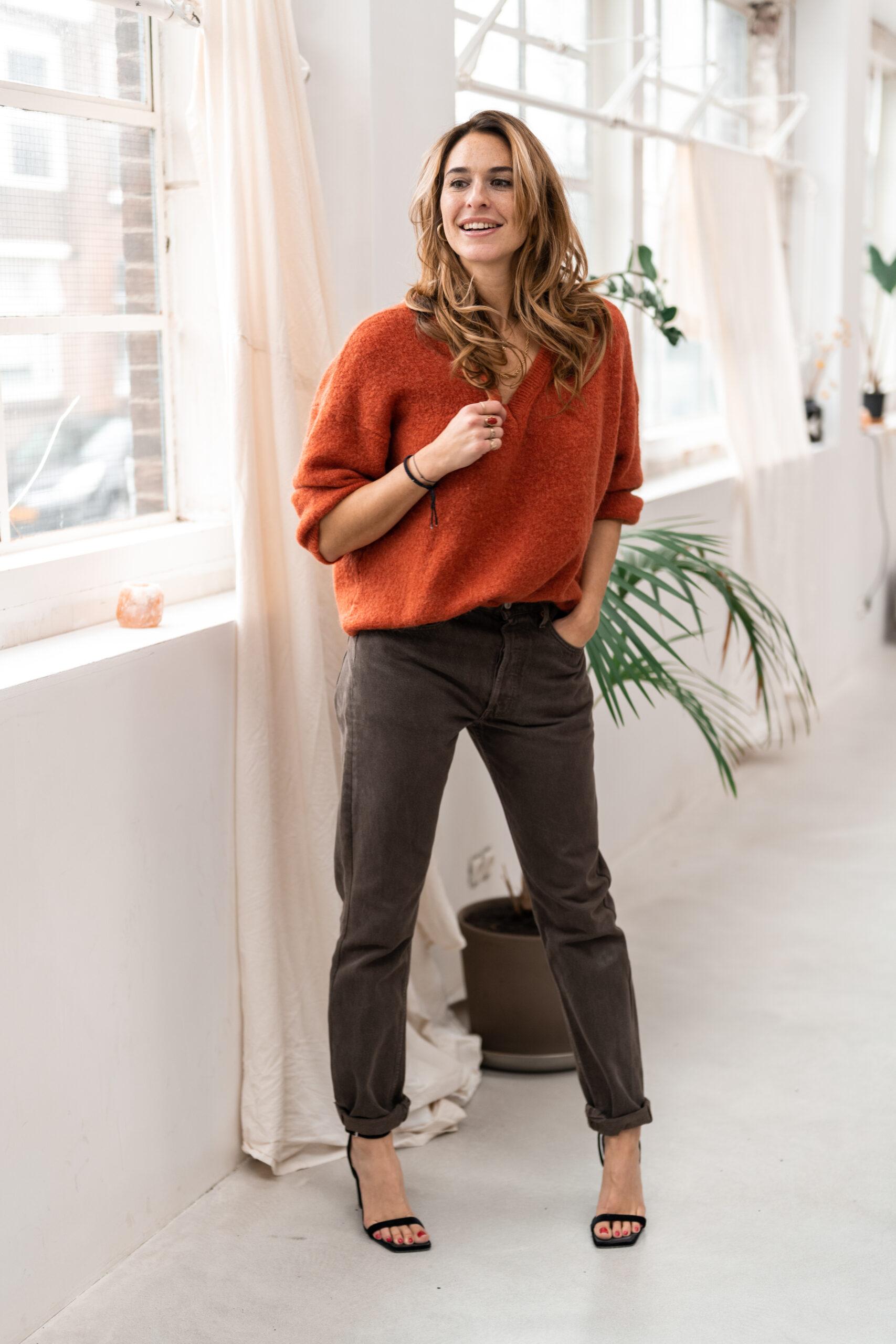 Meisje staat voor een grote raampartij met een oranje trui aan