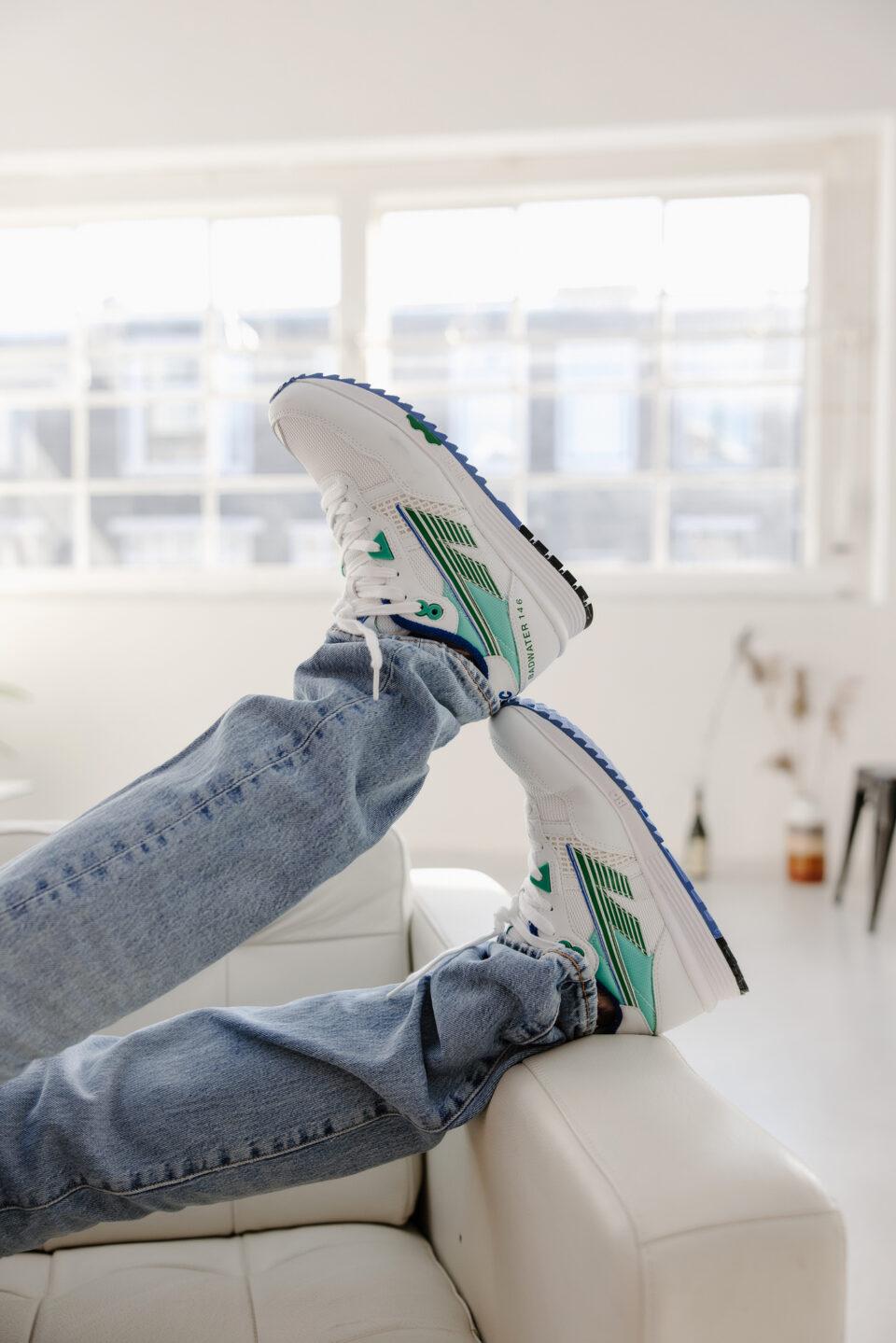 twee benen in een jeans met hi-tec schoenen op de rand van een bank