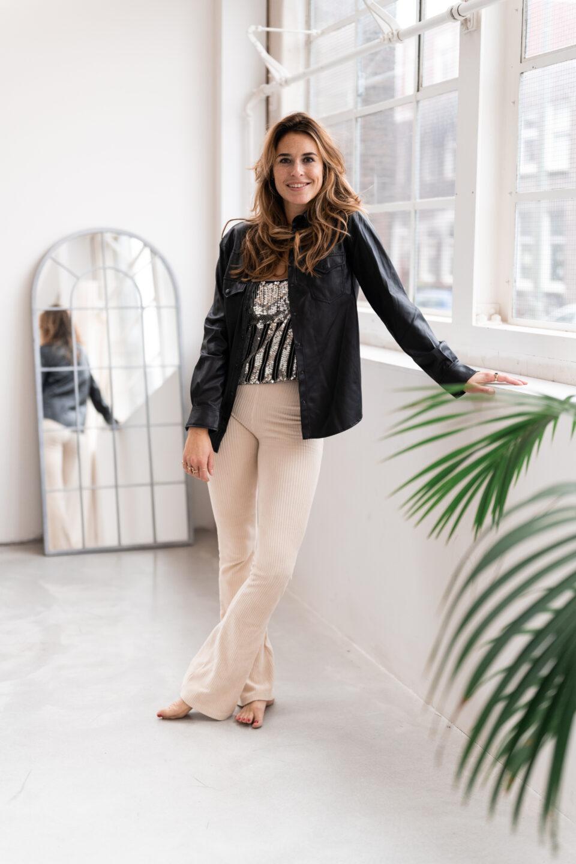 vrouw met beige broek en leren blouse in huiskamer naast raam voor spiegel