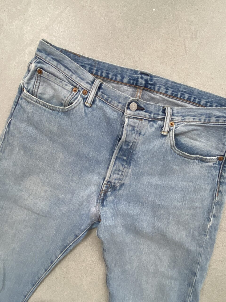 blauwe spijkerbroek op betonvloer
