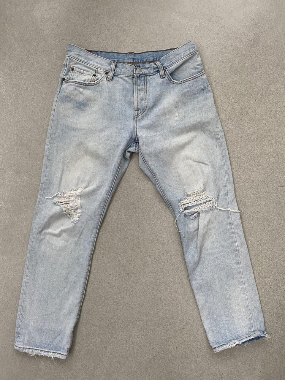 lichtblauwe spijkerbroek op betonvloer