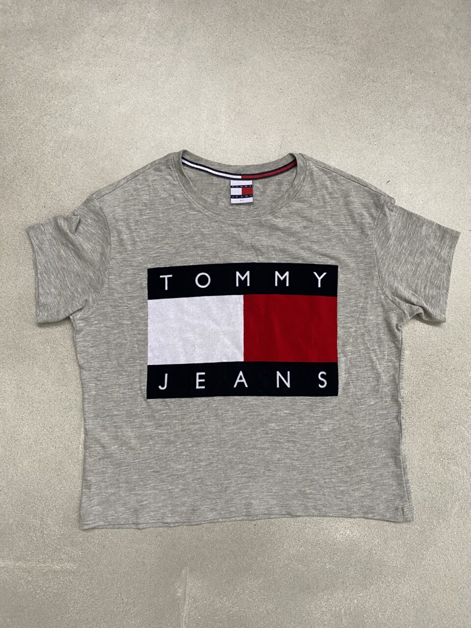 Grijs t-shirt met Tommy Hilfiger logo op betonvloer