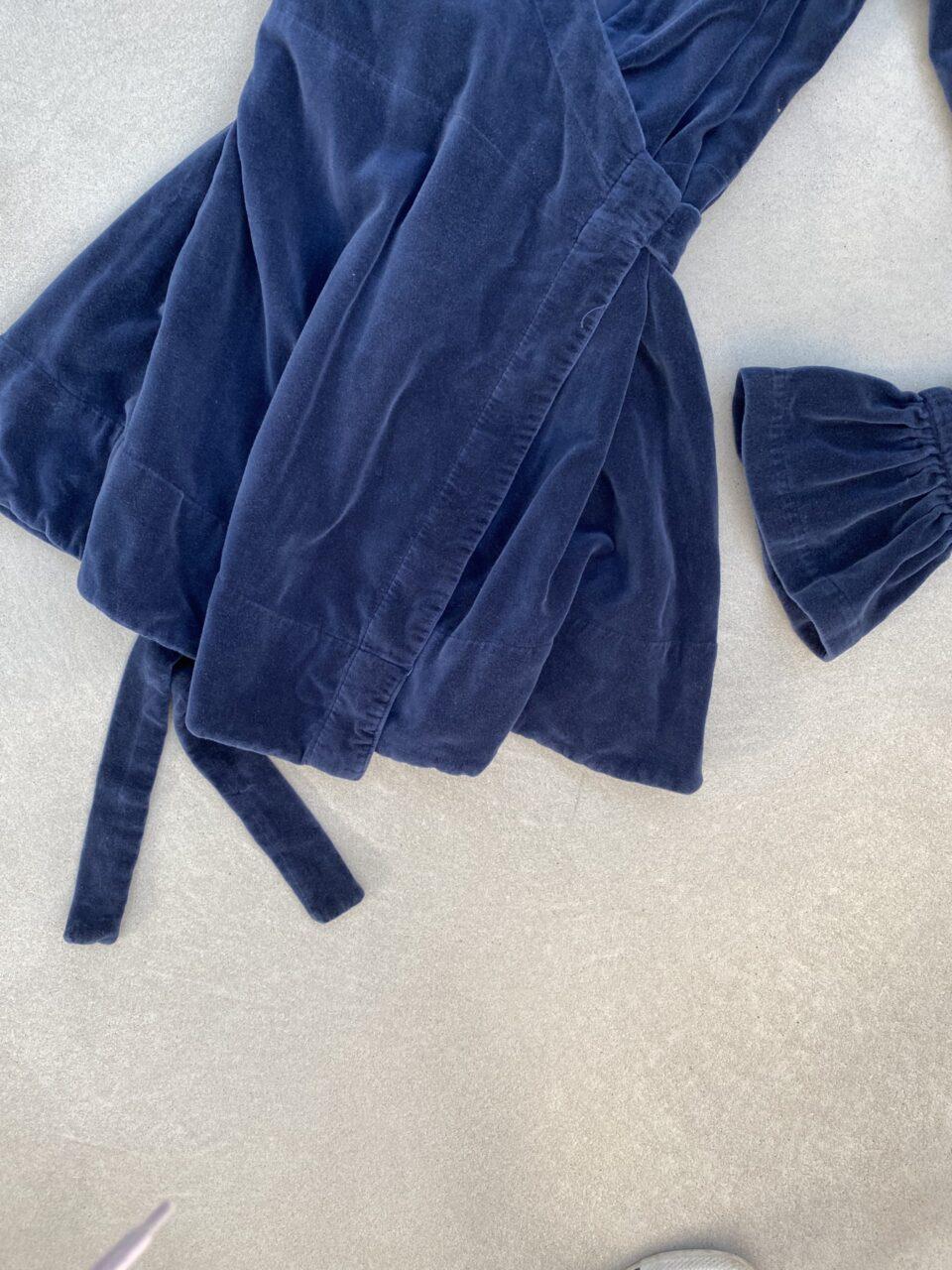 blauw fluwelen jurkje op betonvloer