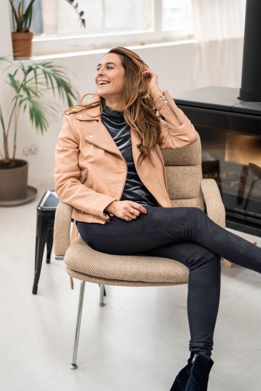 meisje poseert op stoel in cremekleurig jasje